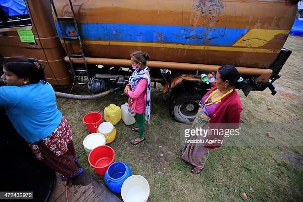Nepalese women wait to fill buckets with water at an earthquake victim camp site in Kathmandu, Nepal on May 7, 2015. The number of the dead in the...
