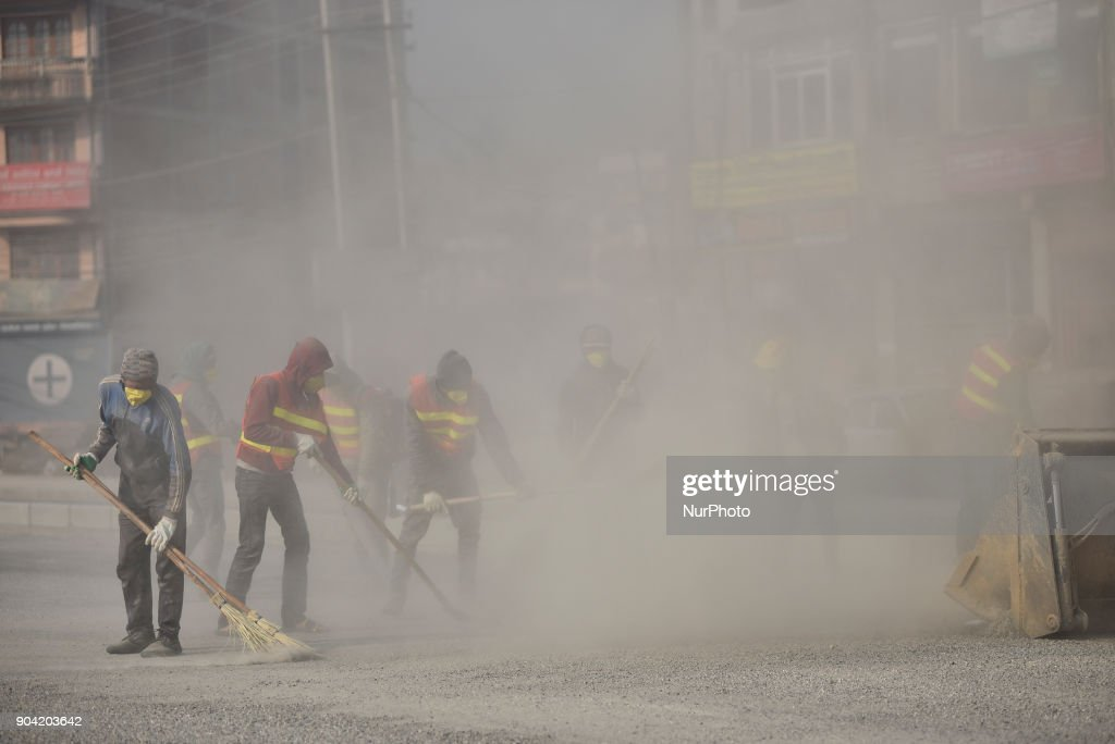 Nepalese worker cleaning road by blowing dust particles for Road construction at Balkumari, Patan, Nepal on Friday, January 12, 2018. The Road Construction project is funded by China AID.