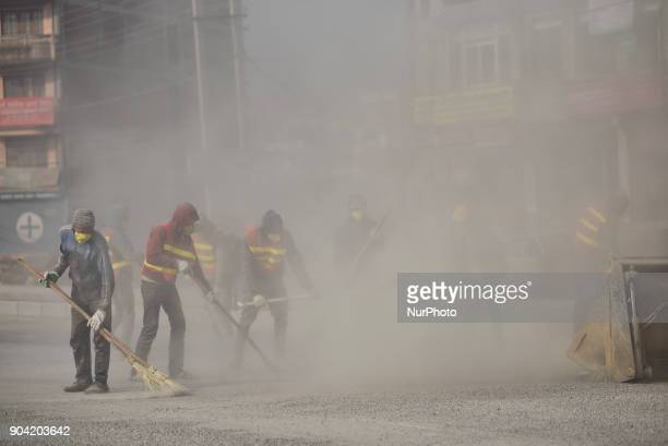 Nepalese worker cleaning road by blowing dust particles for Road construction at Balkumari Patan Nepal on Friday January 12 2018 The Road...