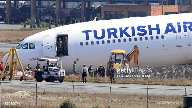 Nepalese workers are seen at the site where a Turkish Airlines plane slid off the tarmac at Kathmandu international airport on March 5 2015...
