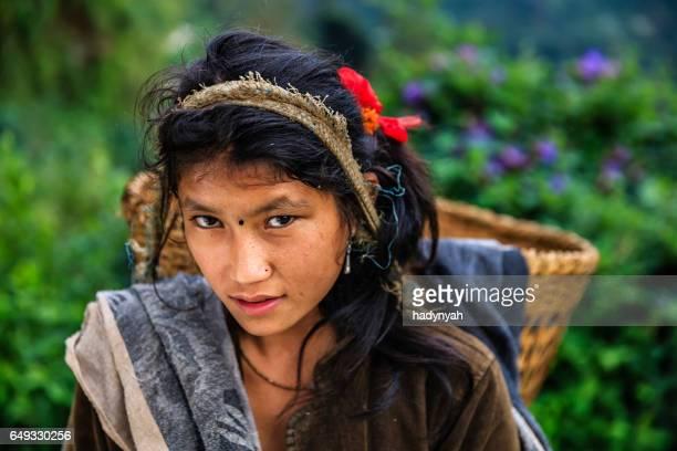 Chica joven Nepal llevando una cesta junto a la gama de Annapurna