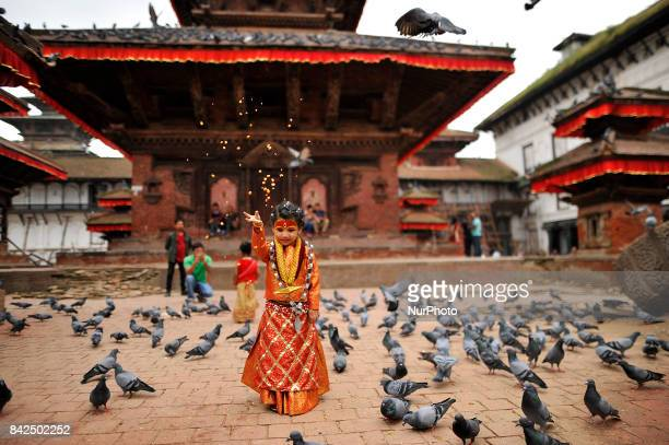 A Nepalese young girl impersonate as a Kumari or living Goddess offering grains towards pigeons during celebration of Kumari puja at Basantapur...