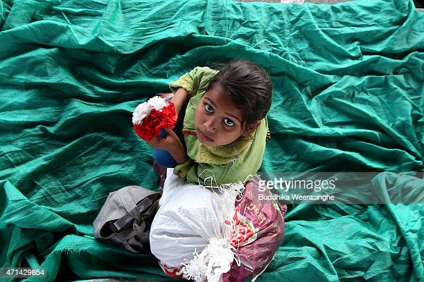 Nepalese young victim of the earthquake looks up at the camera as she waits at a makeshift camp at Tunshikel on April 28, 2015 in Kathmandu, Nepal. A...