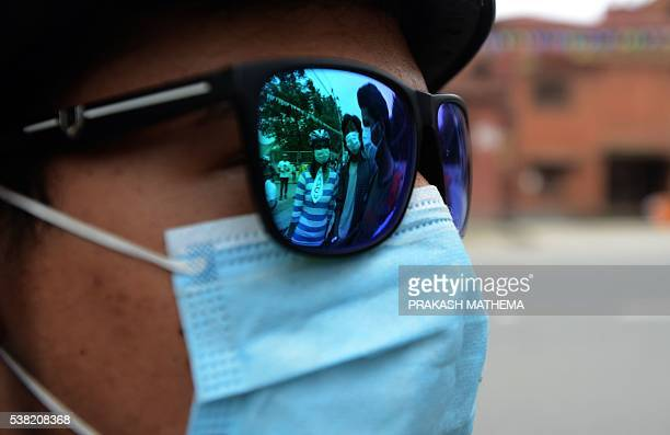 Nepalese youth activists are reflected as they arrive to take part in a World Environment Day event to highlight air pollution in June 5 2016...