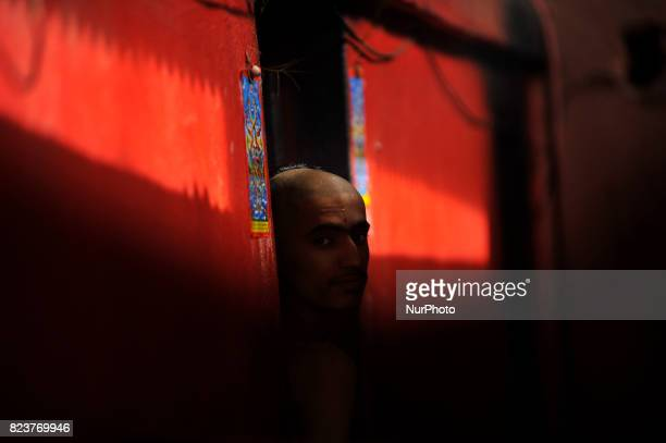 A Nepalese youth from Hindu school Bhagwat Sanyaas Aashram Gurukul peep from door after offering rituals during Nag Panchami festival at...