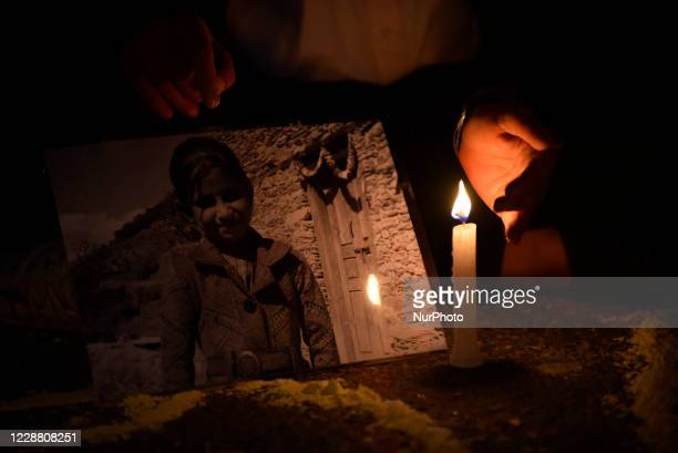 A Nepalese youth hold a poster of 12yrs old Samjhana Kami in a candle light vigil demanding investigation and justice on the memory of Nirmala Panta...