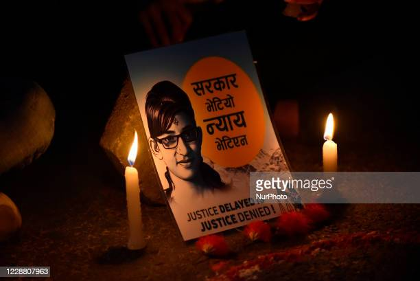 A Nepalese youth hold a poster of Nirmala Panta in a candle light vigil demanding investigation and justice on the memory of Nirmala Panta and...