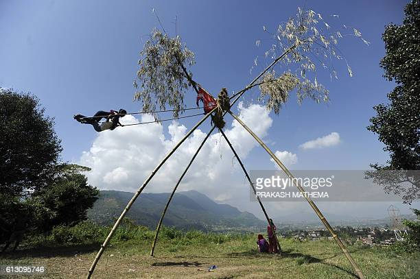 TOPSHOT Nepalese youth play on a swing popularly known as the 'Dashain Ping' on the sixth day of the Hindu festival of Dashain in Lalitpur on the...