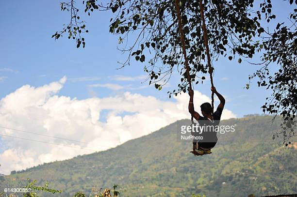 Nepalese youth plays on a traditional bamboo ping or swing during Dashain festival celebration at Kavrepalanchok District Kavre Nepal on Thursday...