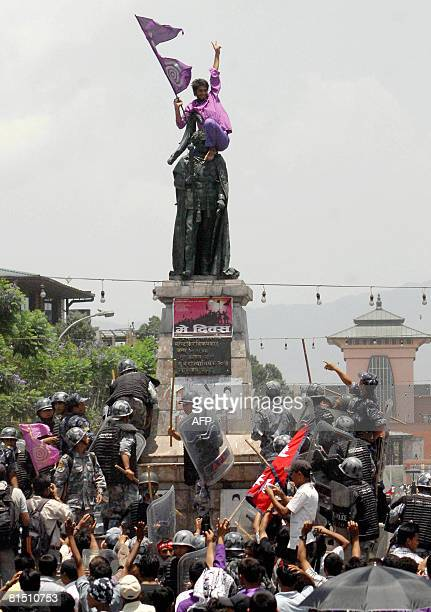 Nepali anti riot police try to detain man carrying the national flag as he sits atop the statute of former king Mahindra outside the royal palace in...
