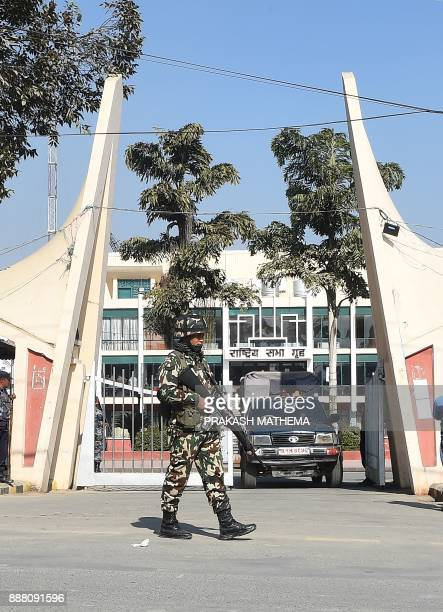 A Nepali army personal stands guard in front of the city hall where election commision officials are counting parliamentary votes in Kathmandu on...