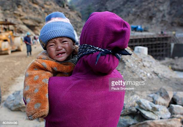 Nepali baby cries as her mother carries her while working on a road widening project March 26 2008 in Chuzom Bhutan Tens of thousands of migrant...