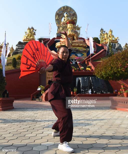 A Nepali Buddhist nun performs kung fu for a demonstration at the Amitabha Drukpa Nunnery during International Women's Day on the outskirts of...