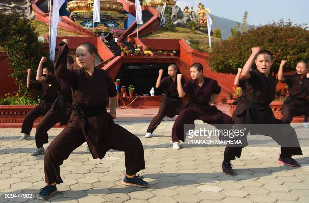 Nepali Buddhist nuns perform kung fu for a demonstration at the Amitabha Drukpa Nunnery during International Women's Day on the outskirts of...