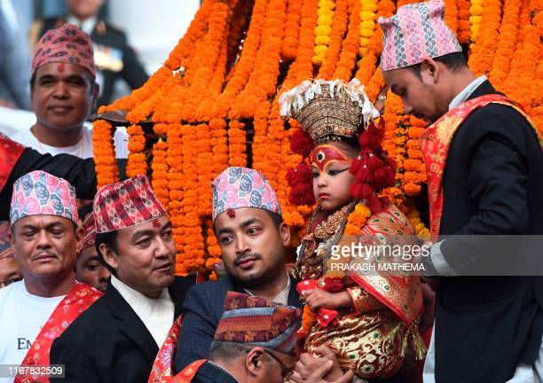 A Nepali child revered as a living goddess or Kumari is carried in a chariot during a procession on the main day of the Indra Jatra festival at...