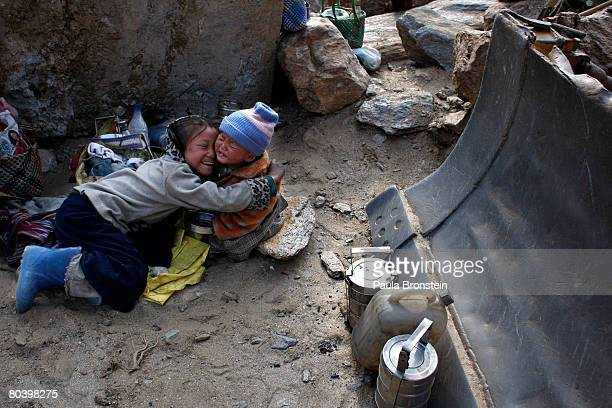 Nepali children play next to a bulldozer while their mothers are busy working on a road widening project March 26 2008 in Chuzom Bhutan Tens of...