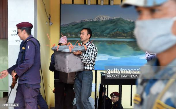 A Nepali election commision official carries a ballot box for vote counting in Kathmandu on December 8 2017 Nepal has just concluded historic...