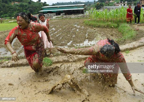 Nepali farmers throw mud at each other in a rice paddy field during National Paddy Day in Lele village on the outskirts of Kathmandu on June 29 2018...