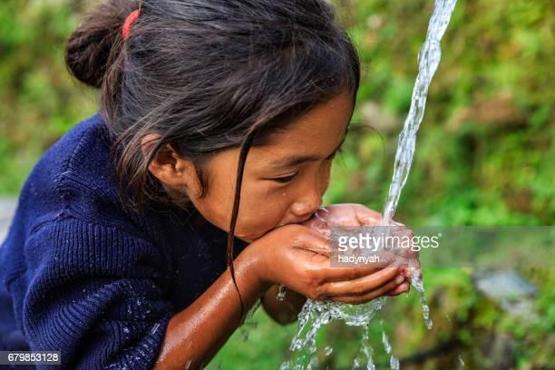 Nepali girl drinking water, village near Annapurna Range