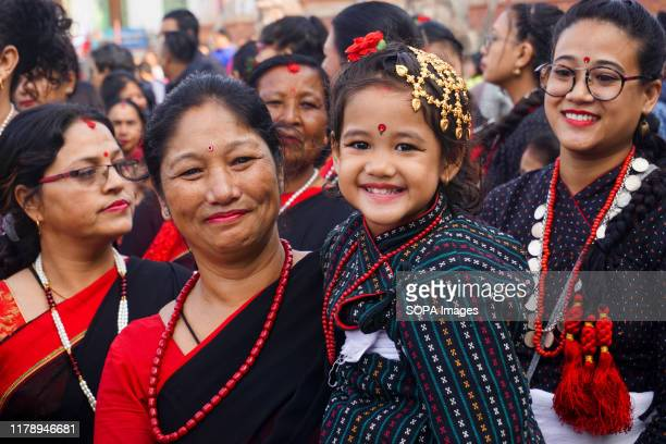 Nepali girl wearing a traditional attire smiles as she is being carried by her mother during the parade to celebrate Nepal Sambat or New Year Newar...