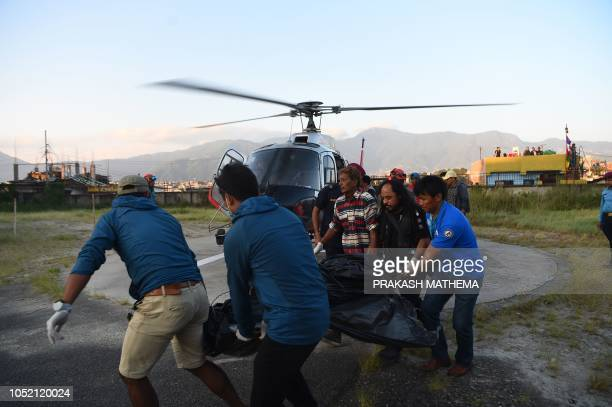 Nepali groundstaff personnel for the Simrik Helicopter company directs a helicopter as the dead bodies of South Korean and Nepali climbers recovered...