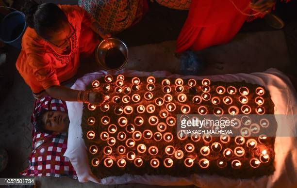 Nepali Hindu devotee lies in a bed covered by 108 lit oil lamps on the tenth day of Dashain in Bhaktapur on the outskirts of Kathmandu on October 19...