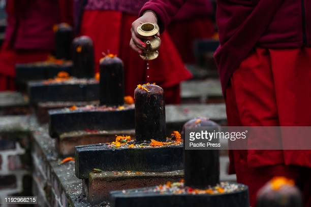 Nepali Hindu devotee offering holy water to a Shiva lingam next to the Shali River during the first day of Swasthani Brata Katha festival in...