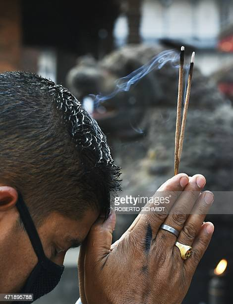 A Nepali Hindu devotee prays with lit incense sticks in front of a statue of Hindu diety Kaal Bhairab in the Durbar Square neighbourhood of Kathmandu...
