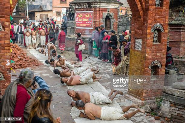 Nepali Hindu devotees offer prayers by rolling on the ground during the Swasthani Brata Katha festival in Bhaktapur Nepal on February 17 2019