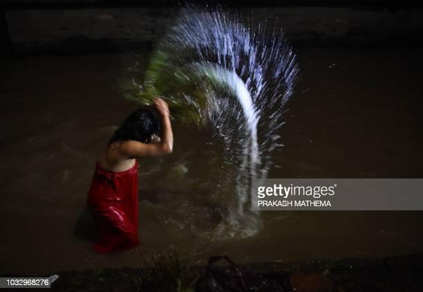 A Nepali Hindu woman takes a ritual bath in the Bagmati river during the Rishi Panchami festival in Kathmandu on September 14 2018 Rishi Panchami...