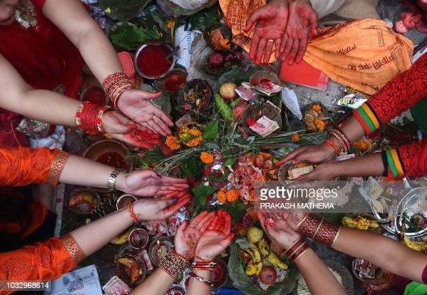 TOPSHOT Nepali Hindu women recite prayers led by a priest as they sit on the banks of the Bagmati River during the Rishi Panchami festival in...
