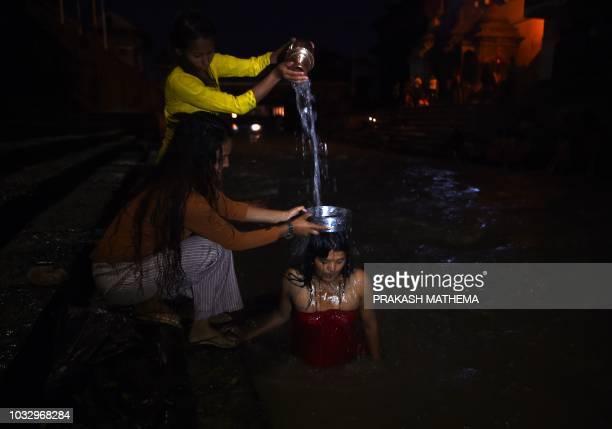 Nepali Hindu women takes a ritual bath in the Bagmati river during the Rishi Panchami festival in Kathmandu on September 14 2018 Rishi Panchami marks...