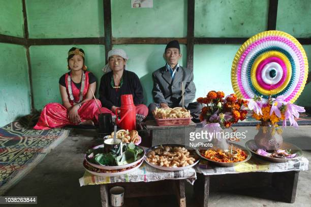 Nepali Limbu couple and their daughter sit in their home by a variety of food prepared for the Bhai Tika Festival in the Khyungte Village in Yuksom...