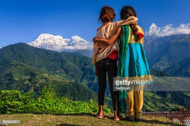 nepali little girls looking at annapurna south - annapurna conservation area stock photos and pictures