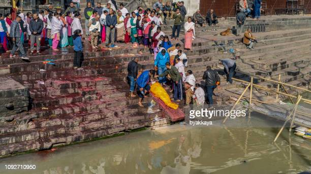 nepali local people during the cremation ceremony along bagmati river - cremation stock pictures, royalty-free photos & images