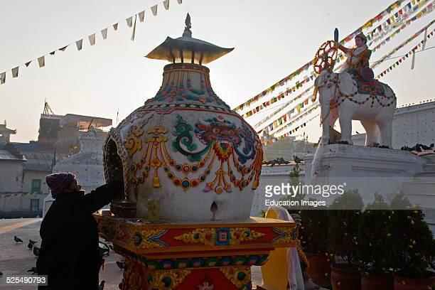 Nepali Man Lights Incense At Bodhanath Stupa In A Burner With Cheppu Guardian Deity Insignias, Kathamandu, Nepal.