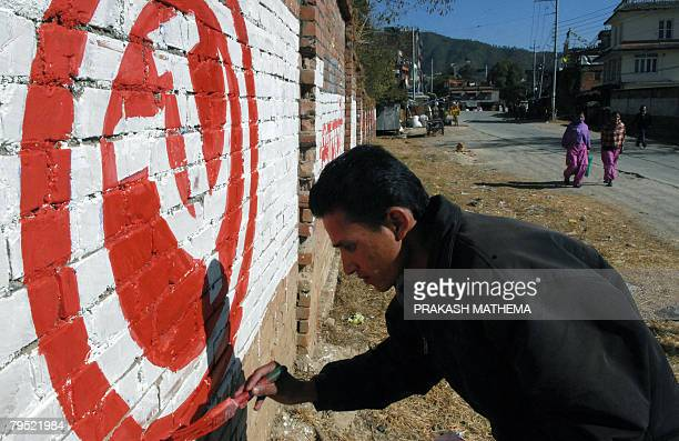 A Nepali man paints a wall with a Maoist symbol and a slogan asking people to vote for the Communist Party of Nepal on the outskirts of Kathmandu on...