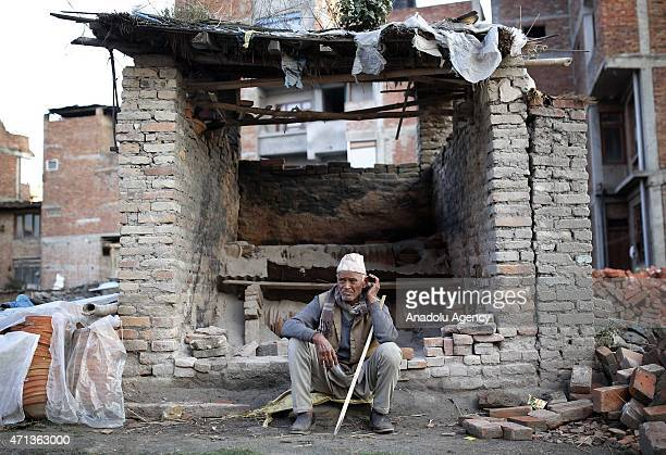 Nepali man sits in front of a destroyed house as people search amidst the rubble of collapsed houses in Bhaktapur, on the outskirts of Kathmandu, on...