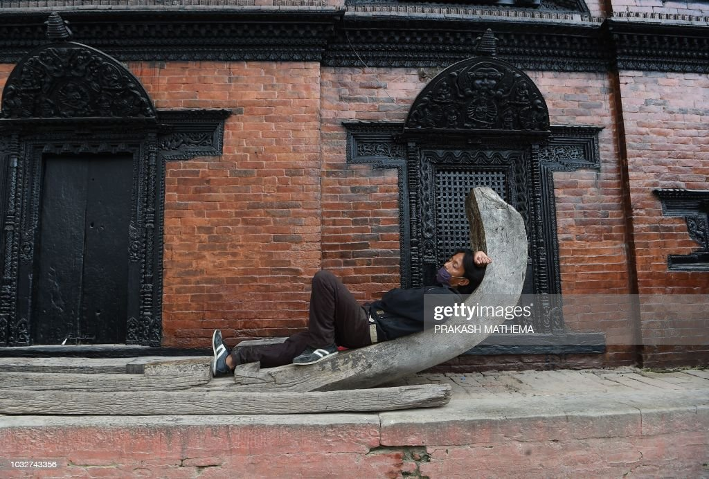 A Nepali man takes a nap in Durbar Square in Kathmandu on September 13, 2018. - Kathmandu Durbar Square is listed as a UNESCO world heritage site.