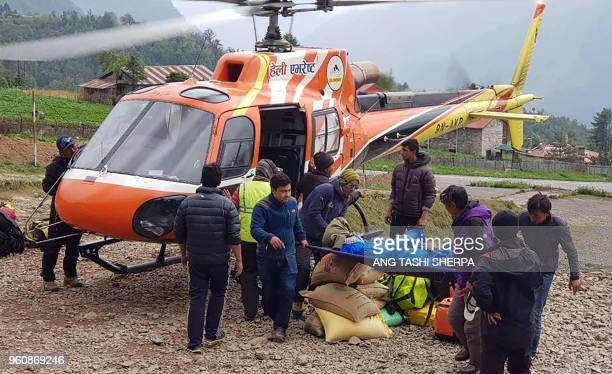 Nepali men carry the body of Japanese climber Nobukazu Kuriki onto a helicopter after it was recovered from Mount Everest at a helipad in Lukla to be...