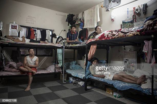 Nepali migrant workers rest after a day of work on foam mattresses between 1 and 8 centimeters thick in a labor camp dormitory in Doha's Industrial...
