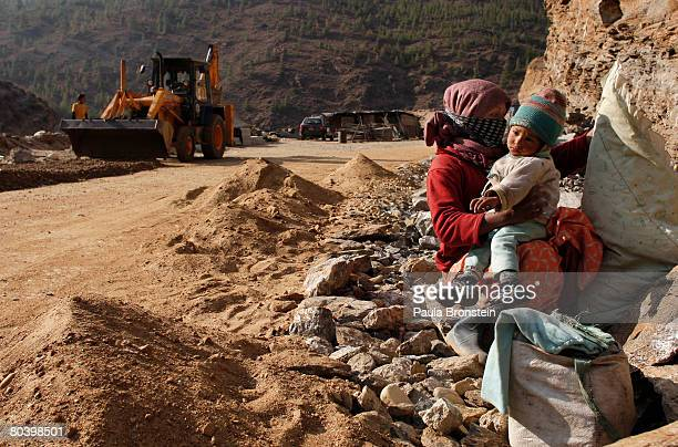 Nepali mother takes care of her child while working on a road widening project March 25 2008 in Thimphu Bhutan Tens of thousands of migrant workers...