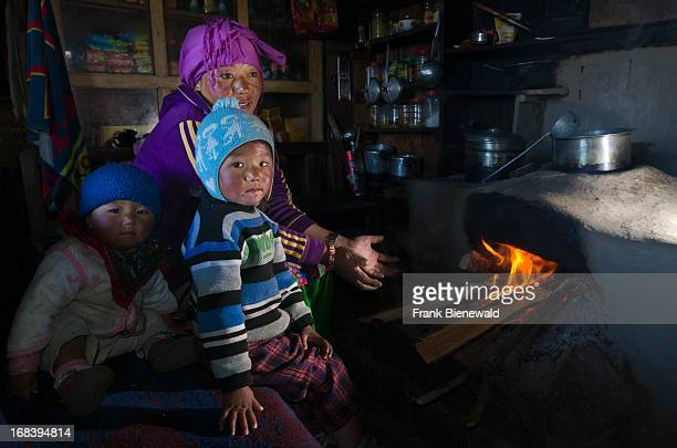 Nepali mother with her two children sitting at the fireplace in their kitchen