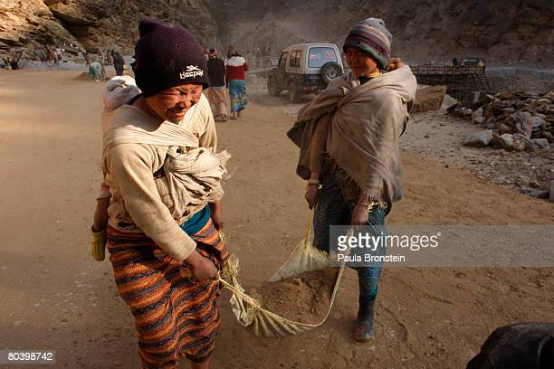 Nepali mothers carry their babies while hauling dirt working on a road widening project March 26 2008 in Chuzom Bhutan Tens of thousands of migrant...