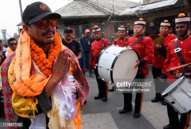 Nepali mountaineer Nirmal Purja gestures as he is welcomed by a music band after arriving at Tribhuvan airport in Nepal's capital Kathmandu on...