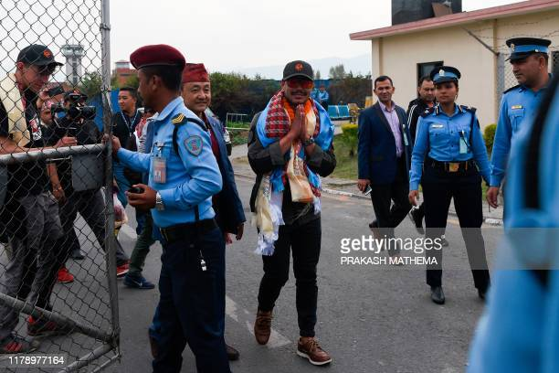 Nepali mountaineer Nirmal Purja greets people as he is welcomed after arriving at Tribhuvan airport in Nepal's capital Kathmandu on October 30 2019 A...