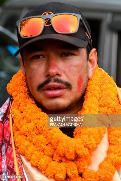 Nepali mountaineer Nirmal Purja looks on after arriving in Tribhuvan airport in Nepal's capital Kathmandu on October 30 2019 A Nepali mountaineer on...