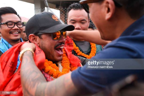 Nepali mountaineer Nirmal Purja reacts as he is garlanded after arriving in Tribhuvan airport in Nepal's capital Kathmandu on October 30 2019 A...