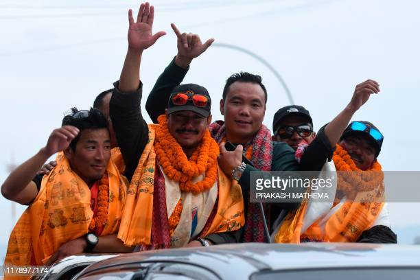 Nepali mountaineer Nirmal Purja waves next to teammate Mingma David Sherpa as they ride atop a vehicle after arriving at Tribhuvan airport in Nepal's...