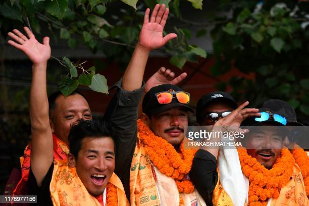 Nepali mountaineer Nirmal Purja waves with teammate Mingma David Sherpa after arriving at Tribhuvan airport in Nepal's capital Kathmandu on October...
